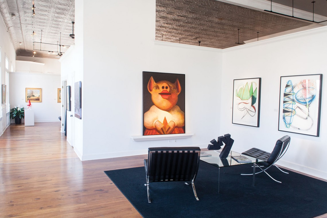 """The private viewing area at Greg Thompson Fine Art offers visitors a quiet place to spend time with a piece of work – in this case, """"Relic"""" (third painting from the right) by Edward Rice."""