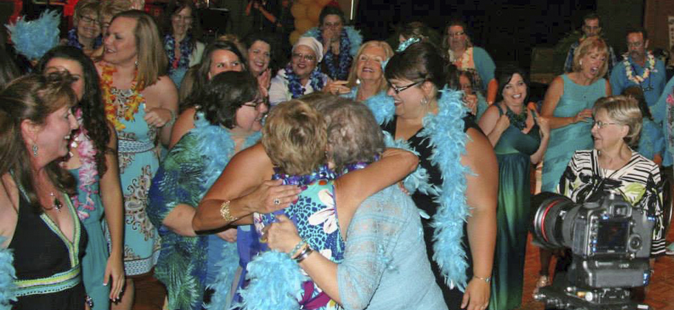 Survivors Embrace After a Surprise Flash Mob Performance at the 2014 Teal Night in Tahiti Event