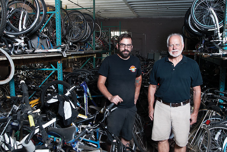 Joe Manero, director of Recycle Bicycles For Kids, with founder Ron King in the middle of one workroom filled with hundreds of bikes ready for a new rider.