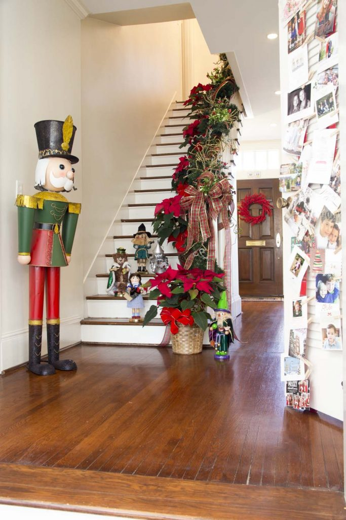 """A Classic Climb ' """"I love Toni's collection of 'The Wizard of Oz' nutcrackers. They're actually a gift from Clarke's mom,"""" Bell said. """"They bring a great touch of whimsy to the formal living space. The banister is dressed with traditional garland, complete with red berries and plaid ribbon."""""""