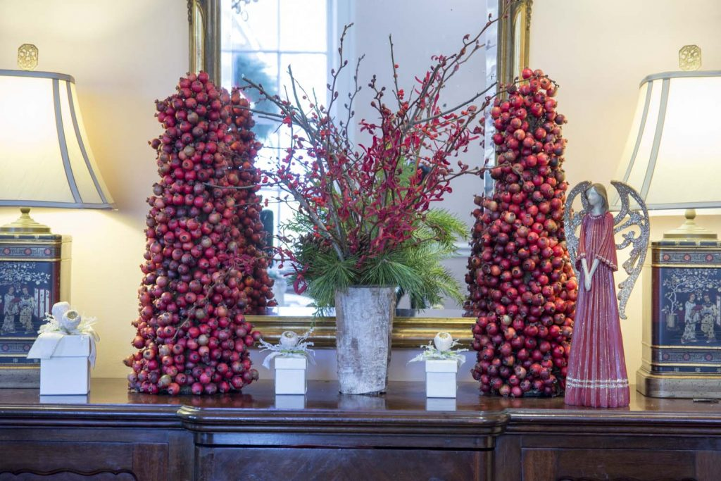 'A Beautiful Buffet The matching antique buffet was dressed with a pair of pomegranate trees that the Tuckers own. Bell added from Tipton Hurst an orchid and holly branch arrangement set in a bark veneer vase and a sweet little crimson angel with glittered wings.