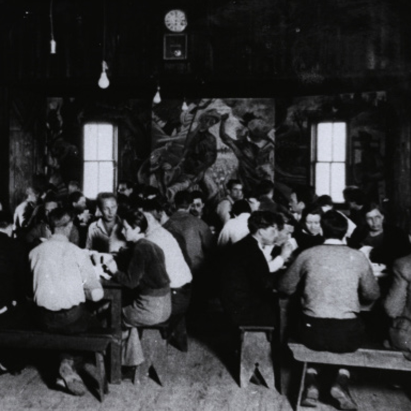 Students gather in the dining hall at the controversial Commonwealth College in Mena. The school was cleared by the FBI of Bolshevism, Sovietism and Communism, but not cleared by Arkansans. Read about the origin of the mural on the wall in Art Scene, pg. 32.
