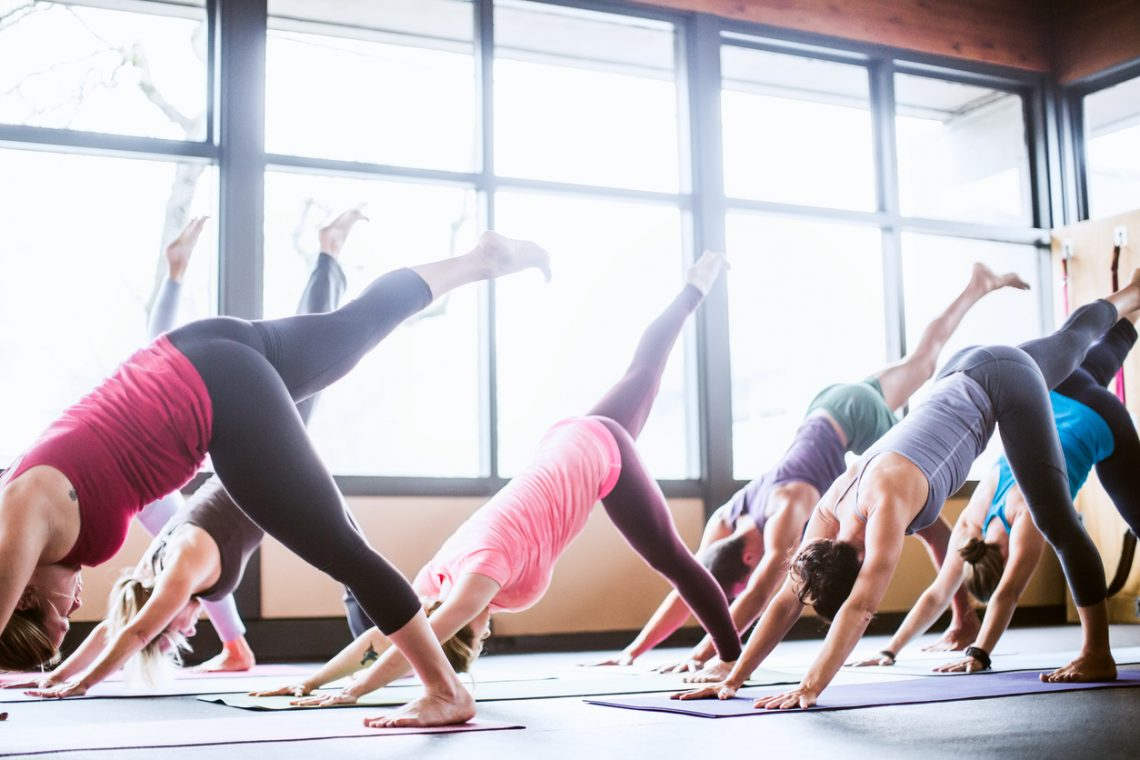 A mixed ethnicity group of men and woman practice different yoga forms and positions in a bright well lit studio.  They are in the one legged downward dog position ( Eka Pada Adho Mukha Svanasana )