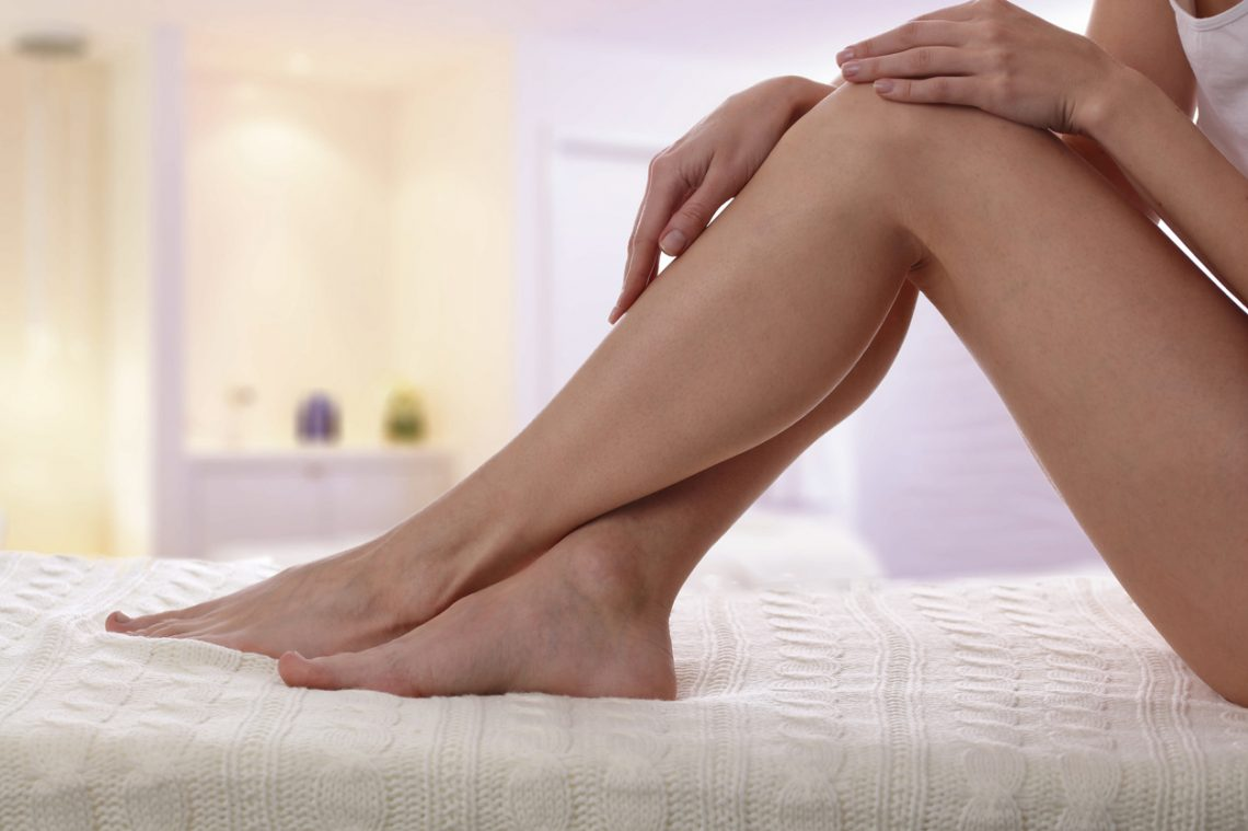 Beautiful, healthy and sensual woman enjoying in a smooth touch of her skin. Female legs Waxing, Hair Removal, Skin care concept