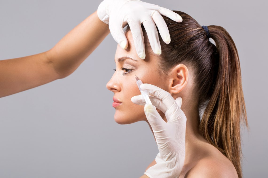 Young woman receiving botox injection.
