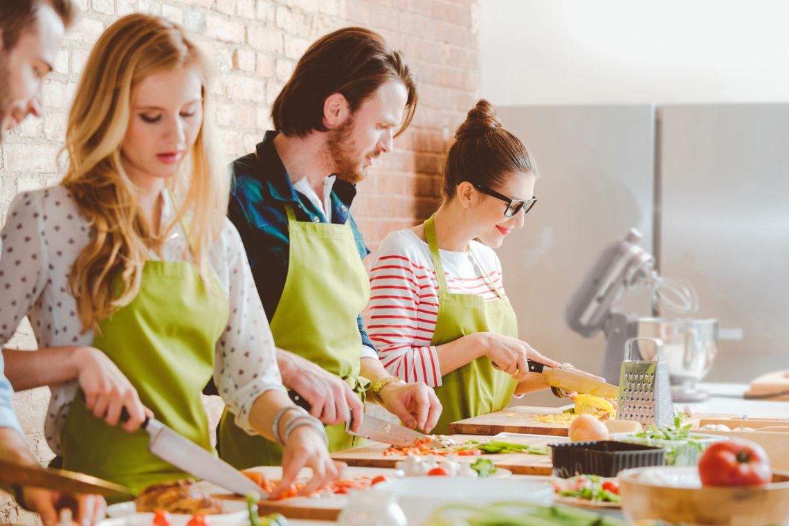 Group of people waering aprons taking part in cooking class, preparing food, slicing vegetables.