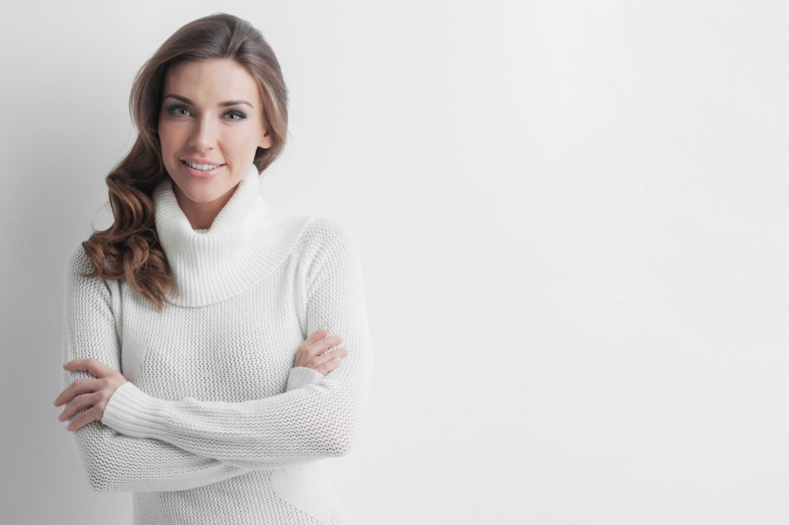 Studio portrait of beautiful long-haired woman in hot sweater on white background