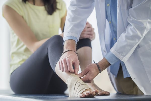 A young Asian woman is getting bandage wrapped around her foot by a male doctor inside a doctor's office. She is in a session for physical therapy.