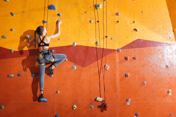 Higher and higher. Attractive young active woman climbing up the wall in gym while training and wearing sportswear and special equipment