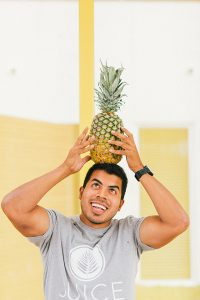 Omar Kasim of Juice Palm stands with a pineapple on his head in front of a yellow background