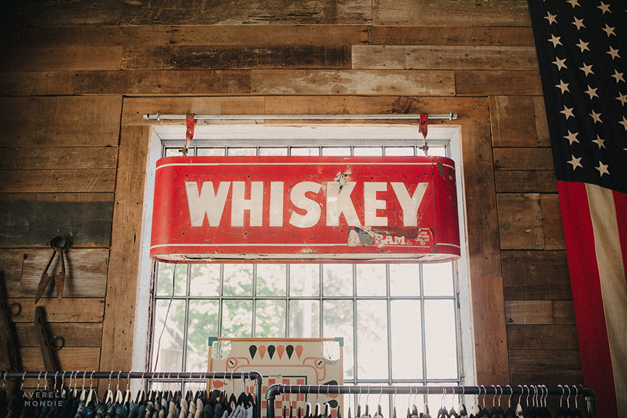 red whiskey sign on window with wooden walls