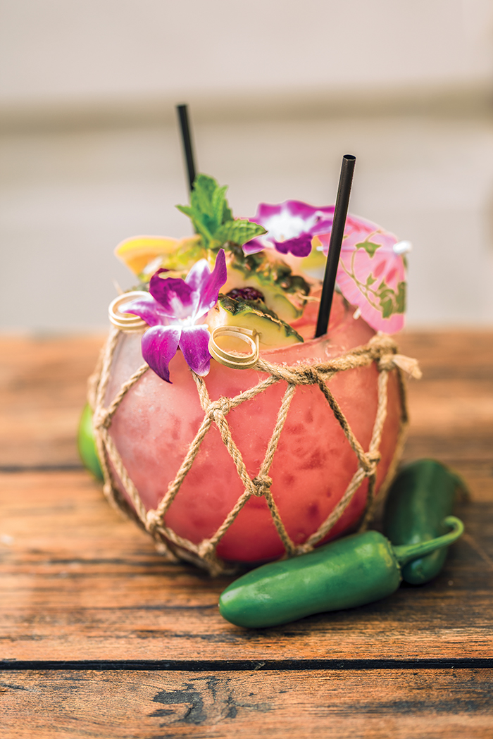 fruity drink on wooden table with peppers and bright purple flowers and pink umbrella