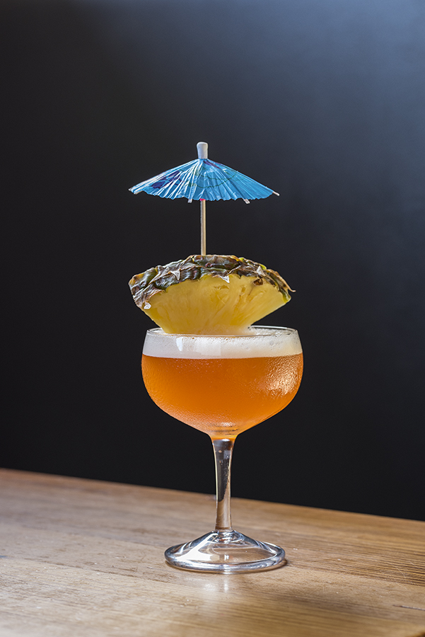 orange drink with pineapple slice and blue umbrella