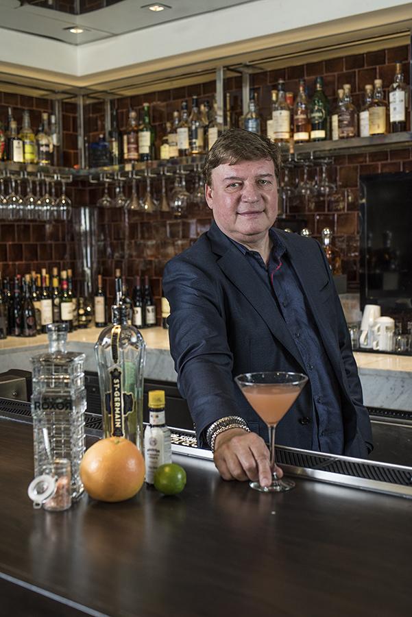 man offering orange drink at a bar