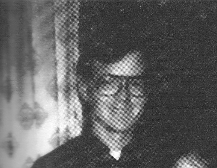 man with glasses in front of curtain