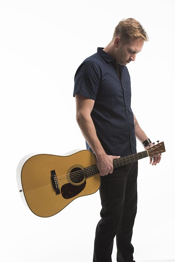 man carrying guitar