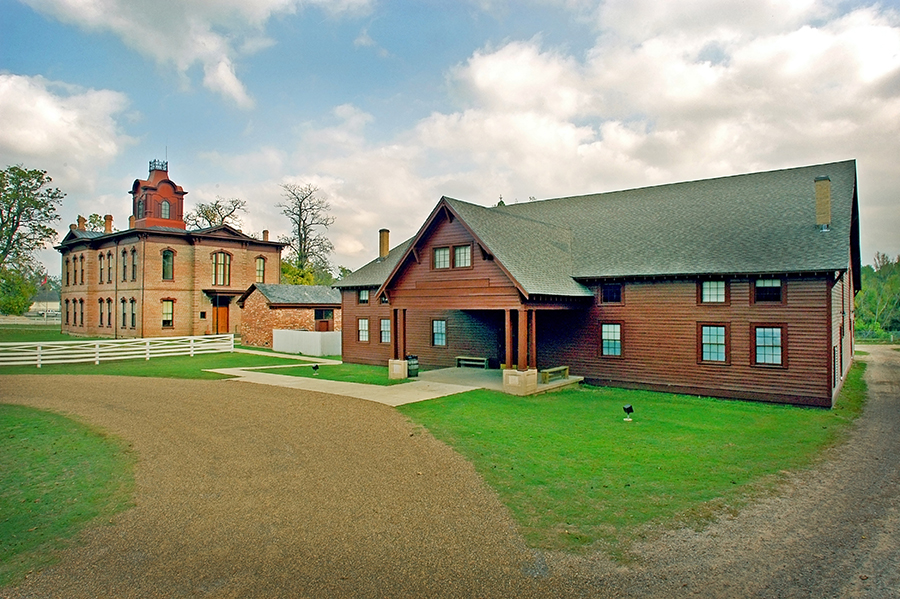 wooden building with green grass and driveway