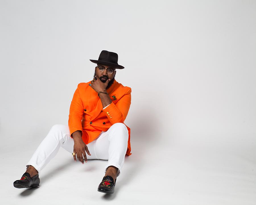 man in black hat wearing orange shirt and white pants