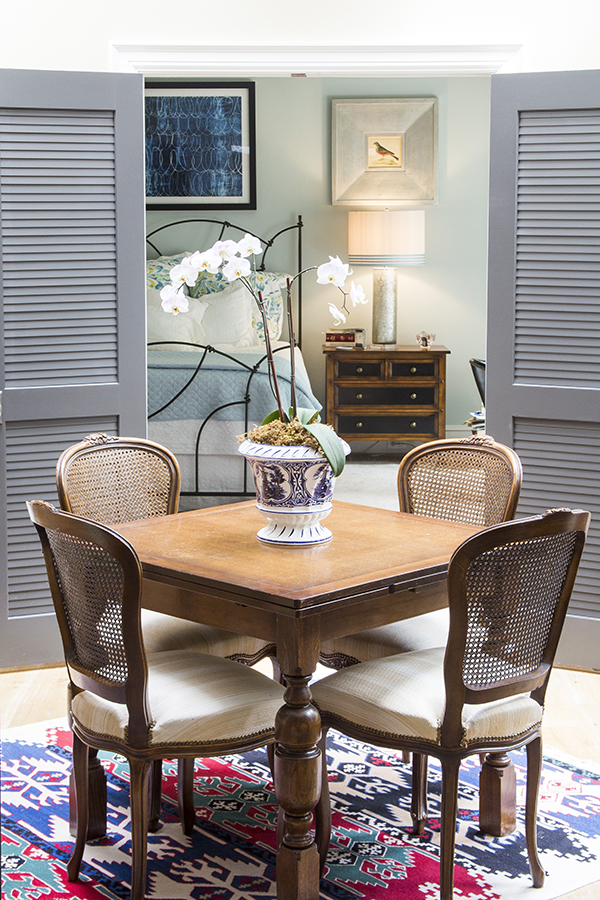 table with 4 chairs and shutter doors behind