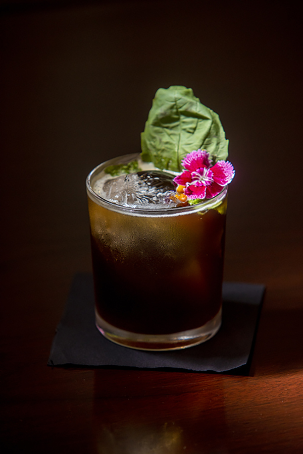 dark drink with pink flower and ice on brown background