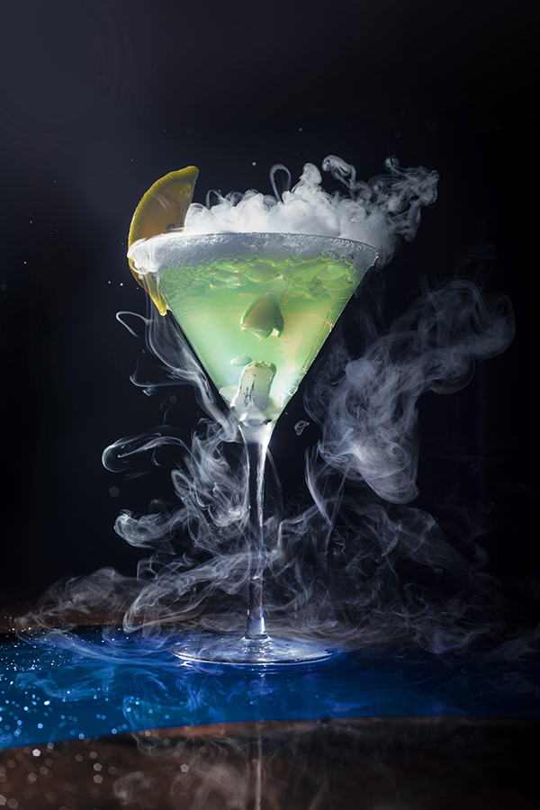 lime green drink with lemon and smoke with black background