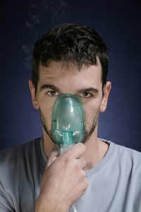 Young man with inhalation mask.Desatureted