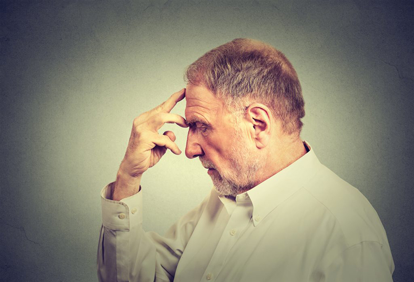 Closeup portrait of a senior thoughtful man isolated on gray wall background