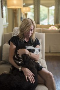 Woman holding cute dog in home