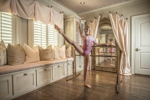 Young girl doing ballet in bedroom with wood floors and pillows in front of windows