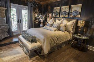 Dark bedroom with pillows, door and artwork with wood floor