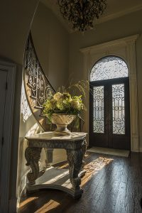 Beautiful entry way with double doors, staircase and flowers on a table with wooden floors