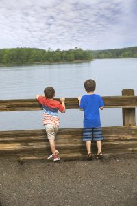 Two kids standing at fence looking at water