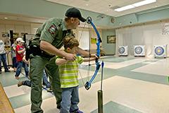 Man and boy shooting bow and arrow