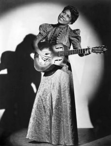 Woman singing and playing guitar in black and white