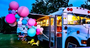 Bus with bright balloons at night