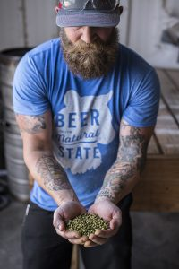man in blue shirt holding grain