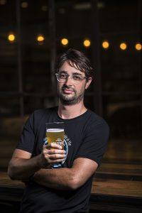 man holding beer in dark room