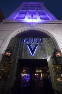 Vault logo on doorway outside at night