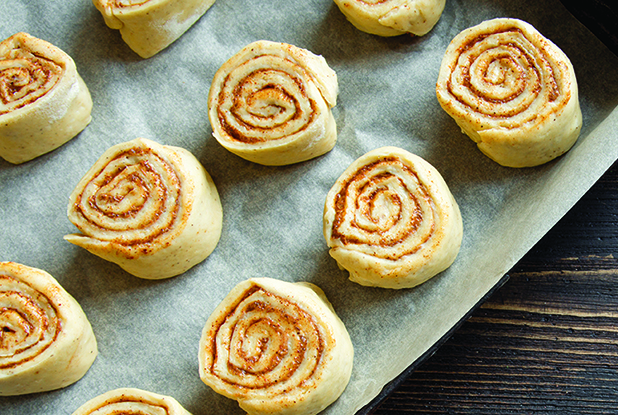 Cinnamon rolls or cinnabon, homemade recipe raw dough preparation sweet traditional dessert buns pastry food. Food ingridients for cinnamon rolls, flat lay on wooden table, copy space.